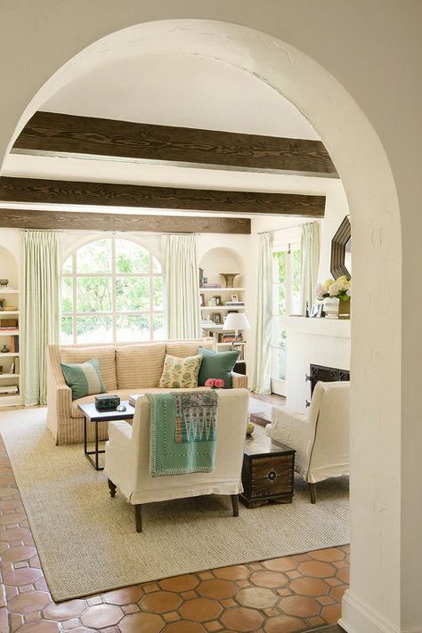 a charming living room with wooden beams and an arched doorway that set the tone in the space