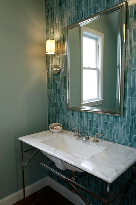a chic vintage-inspired bathroom with mint green walls and a turquoise skinny tile wall plus a marble clad sink