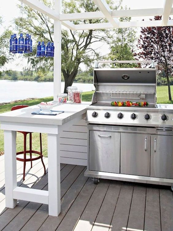 an outdoor grill plus some eating space and blue bottles hanging over it