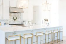 15 very elegant gold stools with white seats highlight the kitchen design and echo with the pendant lamps