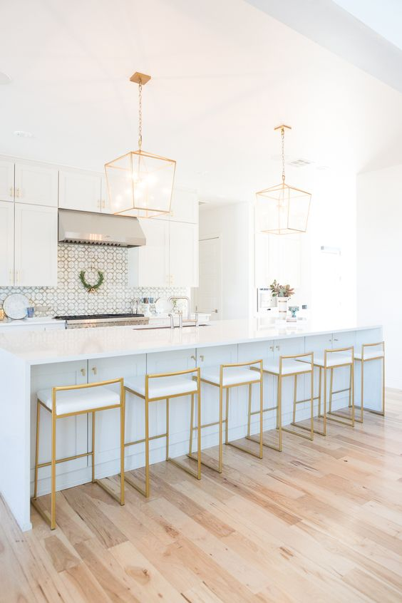 very elegant gold stools with white seats highlight the kitchen design and echo with the pendant lamps