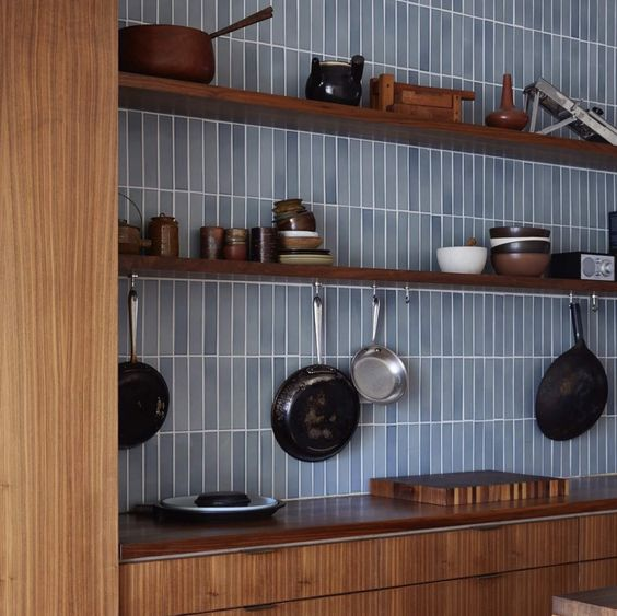 warm-toned wooden cabinets paired with a light blue skinny tile backsplash look contrasting and refreshed