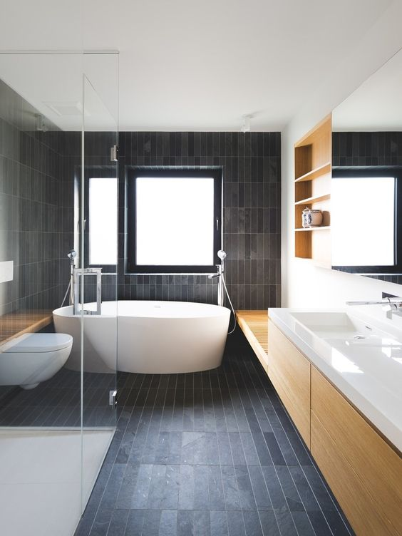 a contemporary bathroom all clad with matte dark skinny tiles and refreshed with light colored wood and white pieces