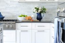 16 white modern cabinets, grey countertops and grey marble skinny tiles on the backsplash for a neutral and welcoming kitchen