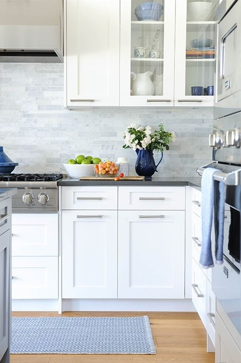 white modern cabinets, grey countertops and grey marble skinny tiles on the backsplash for a neutral and welcoming kitchen