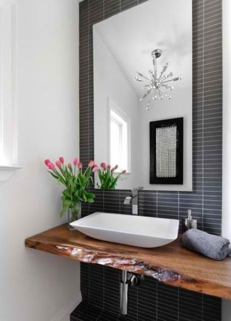 a contemporary bathroom with a navy skinny tile statement wall, a live edge floating vanity and a geometric sink