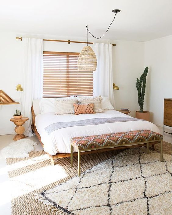 a desert boho bedroom with a wicker lamp over the bed to highlight its relaxed boho styling