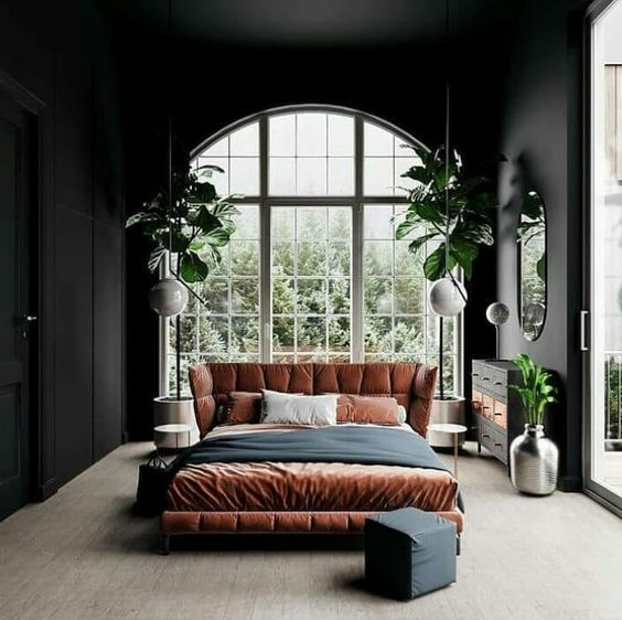 a trendy boho bedroom done in neutrals, black, rust and greenery with an arched window that takes the whole wall