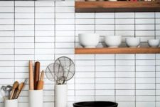 17 white skinny tiles accented with black grout highlight the contemporary style of the kitchen