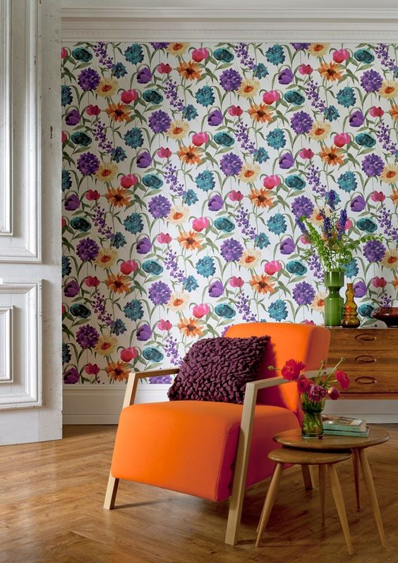 a colorful floral wallpaper wall matches the mid century modern space and cheers it up at the same time