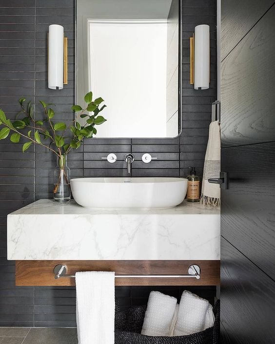a contemporary bathroom with matte black skinny tiles on the wall plus a floating wood and marble vanity