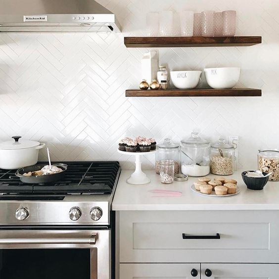 a contemporary kitchen with white skinny tiles on the backsplash and grey cabinets plus white countertops