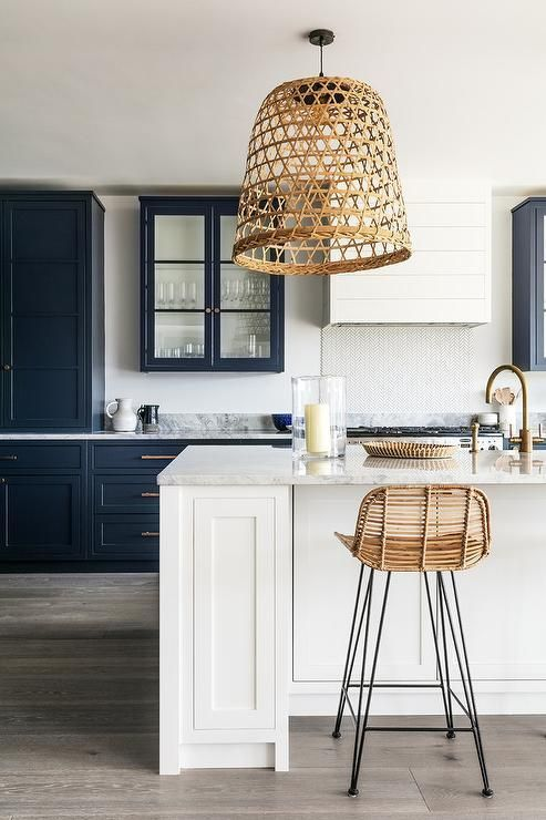 a crispy kitchen in black and white looks contrasting and bold and a wicker lampshade and a rattan chair add a relaxed feel