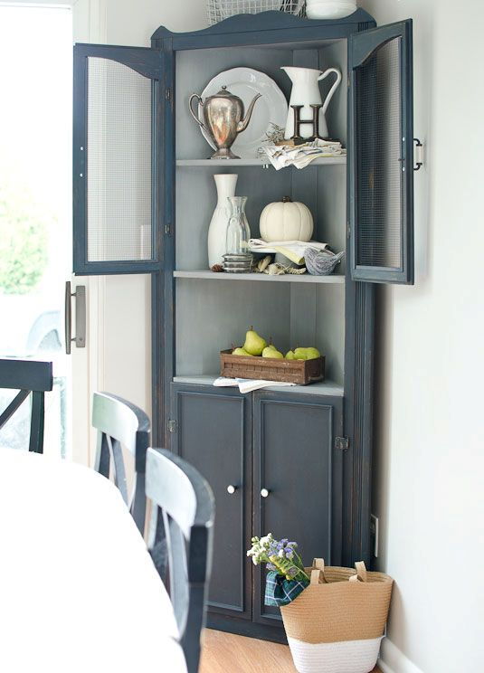 a graphite grey corner cabinet for storage and displaying any decorative objects