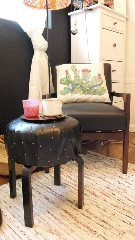 an IKEA Frosta stool turned into a chic small ottoman covered with black leather with a shiny touch