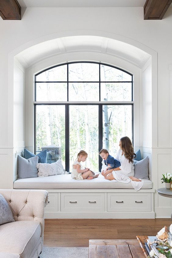 an arched window features an upholstered bench, some drawers and pillows for storage