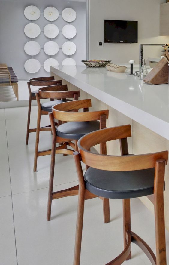 bold wood and leather stools spruce up a neutral space and add a bit of drama to the kitchen