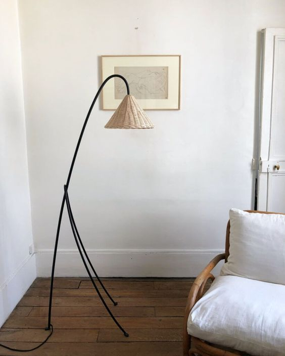 a catchy black metal floor lamp with a tiny wicker lampshade for a natural and coastal feel in the space