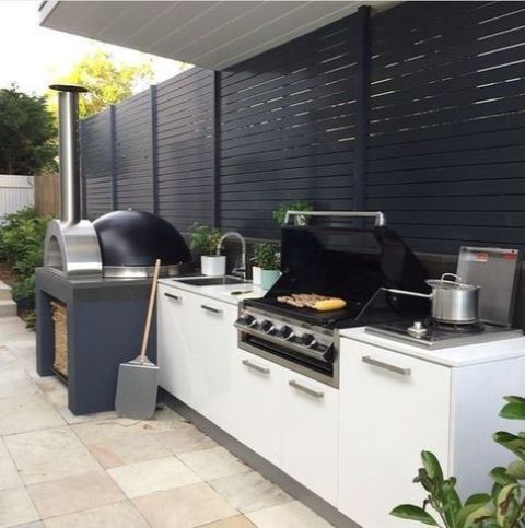 a contemporary outdoor kitchen with a grill and a pizza oven is a great idea for every patio