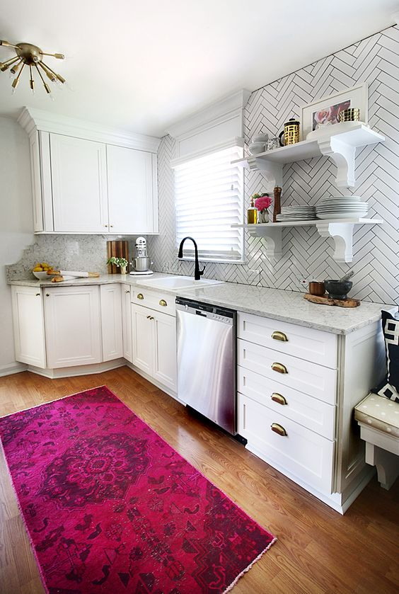 a contemporary white kitchen with stone countertops and white skinny tiles highlighted with black grout looks very nice