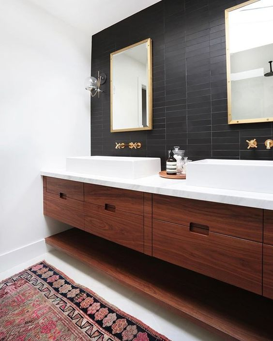 a mid-century modern bathroom with black skinny tiles on the accent wall that contrast white sinks