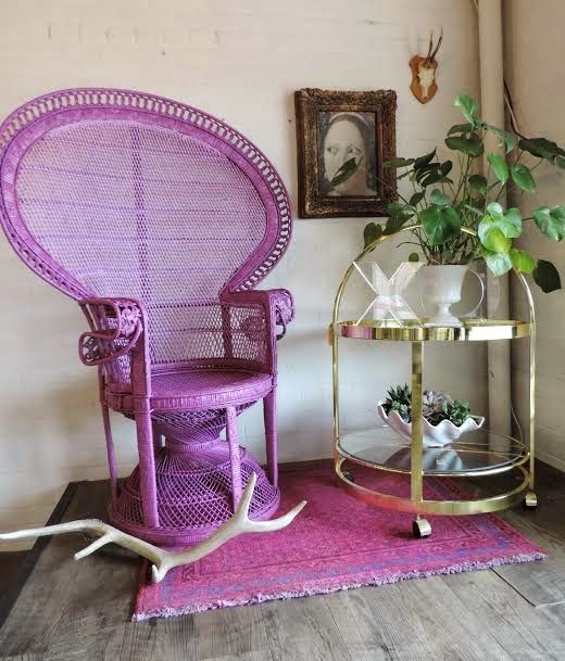 a purple peacock chair and a matching rug is a bright and non-traditional idea