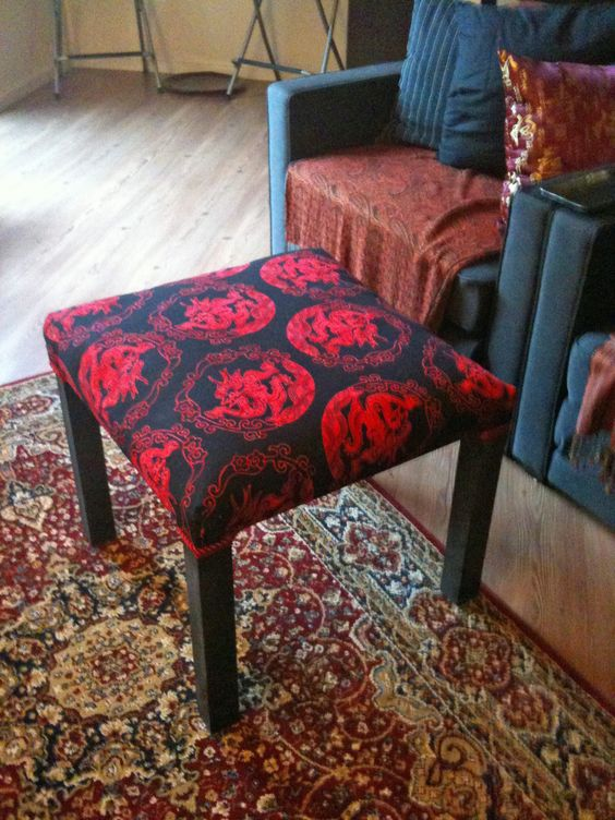 an IKEA Lack table renovated with bright black and red printed fabric on top to use as a footstool or ottoman