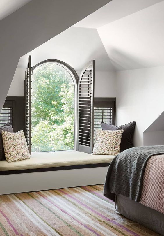 an attic bedroom with a small arched window that adds chic to the space and makes it inviting