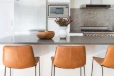 19 chic brown leather stools with black metal legs look very chic and add a textural touch to the space