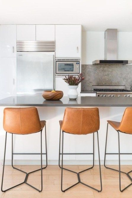 chic brown leather stools with black metal legs look very chic and add a textural touch to the space