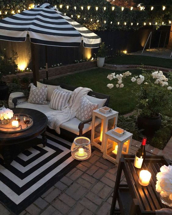 a cozy patio with a striped rug, candle lanterns and potted blooms that refresh the look