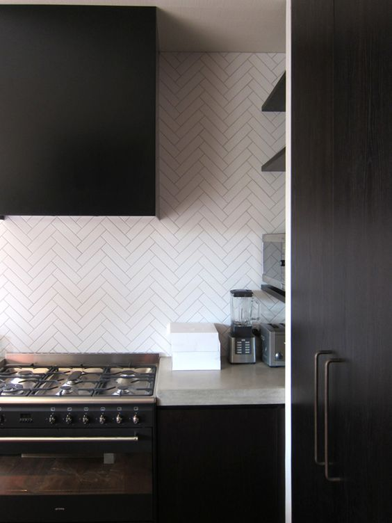 a dark minimalist kitchen done with concrete countertops and white skinny tiles clad in a chevron pattern for a catchy look
