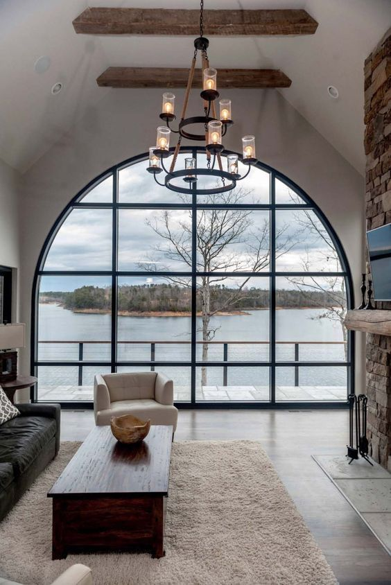 a living room with an oversized arched window that brings a gorgeous view inside