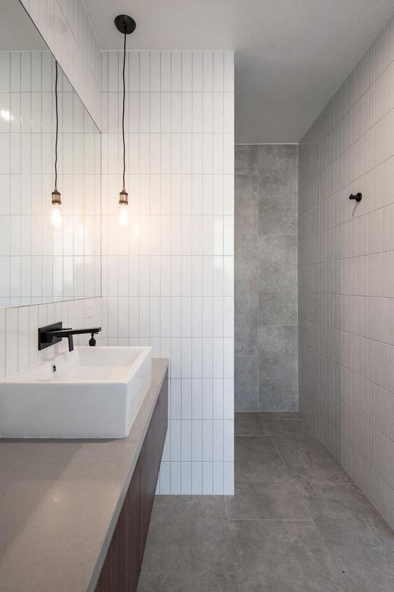 a minimalist bathroom done with grey tiles and white skinny ones for an eye-catchy touch