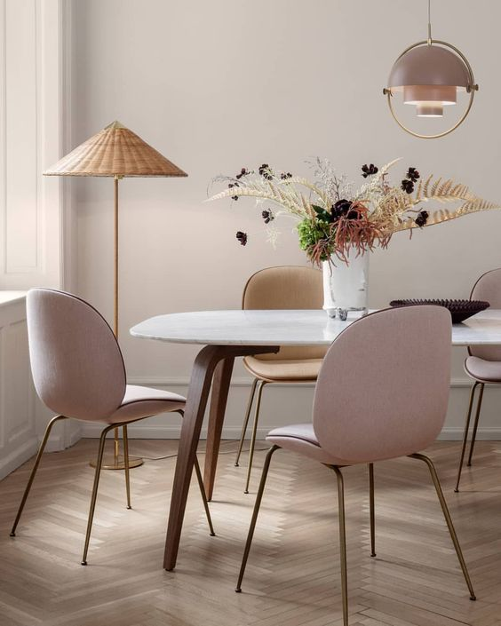 an elegant mid-century modern dining space with blush chairs and a wicker floor lamp to add a relaxed feel to the room