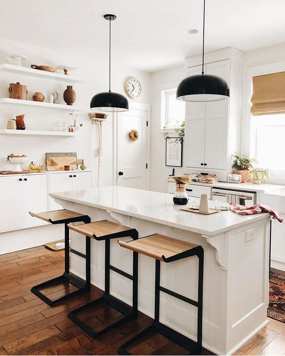 bold dark metal and light-stained wood stools add a touch of drama to the neutral kitchen and pendant lamps continue that