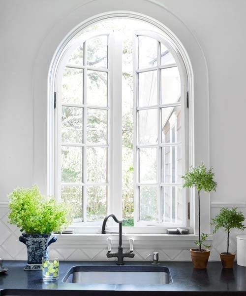 a beautiful arched window accents the farmhouse style and adds personality to the space