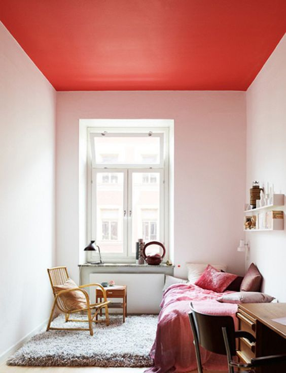 a chic bedroom done in neutrals with a bright red ceiling and bold red bedding to match