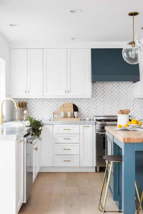 a gorgeous modern kitchen with teal and blue accents, butchblock tabletop and a white skinny tile backsplash in a chevron pattern