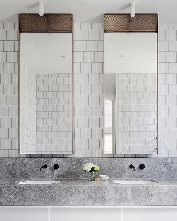 a minimalist sink space with white skinny tiles on the wall, catchy mirrors, a grey marble vanity