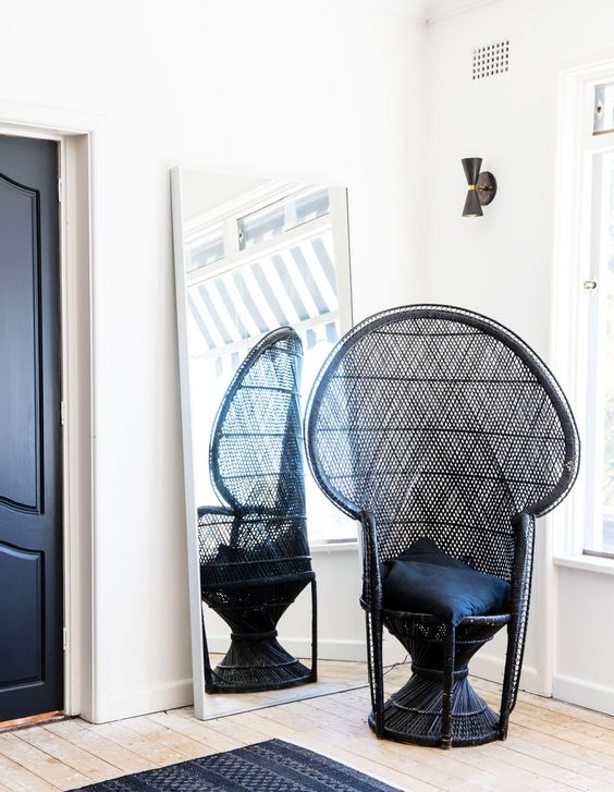 a single black peacock chair with black pillows will match a monochromatic space giving it a slight boho feel