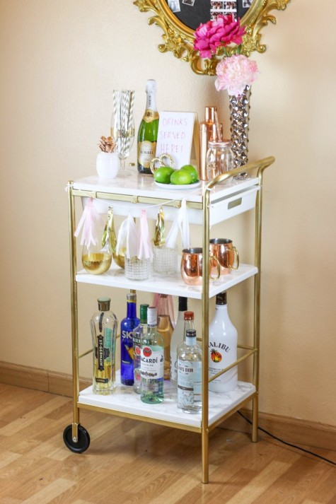 an IKEA Bygel cart hacked with gold spray paint and marble contact paper is a chic and glam piece