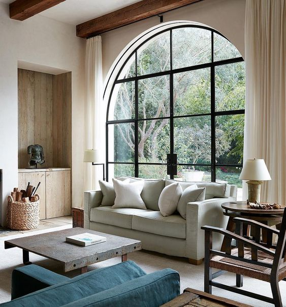 a contemporary living room with an oversized black frame arched window that includes an access to the garden