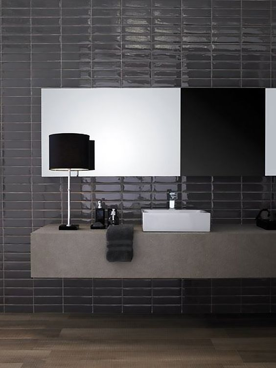 a moody bathroom with black skinny and shiny tiles on the wall and a concrete floating vanity for a contrast