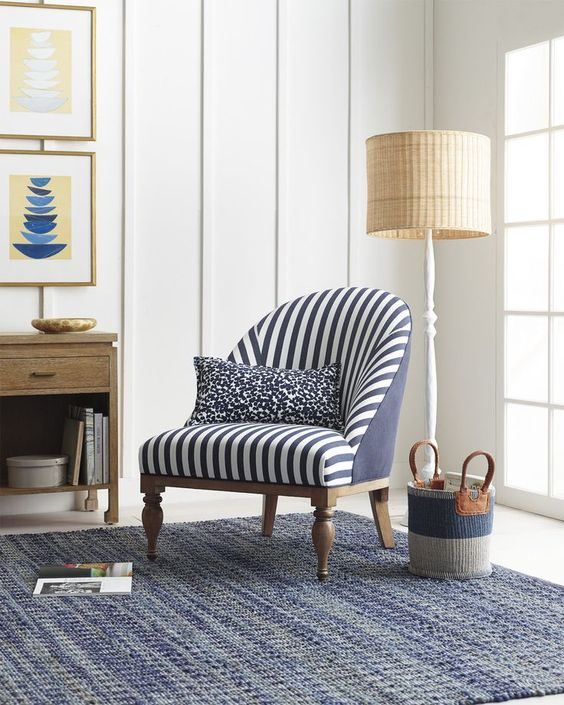 a nautical nook with a classic striped chair and a vintage inspired floor lamp with a wicker lampshade