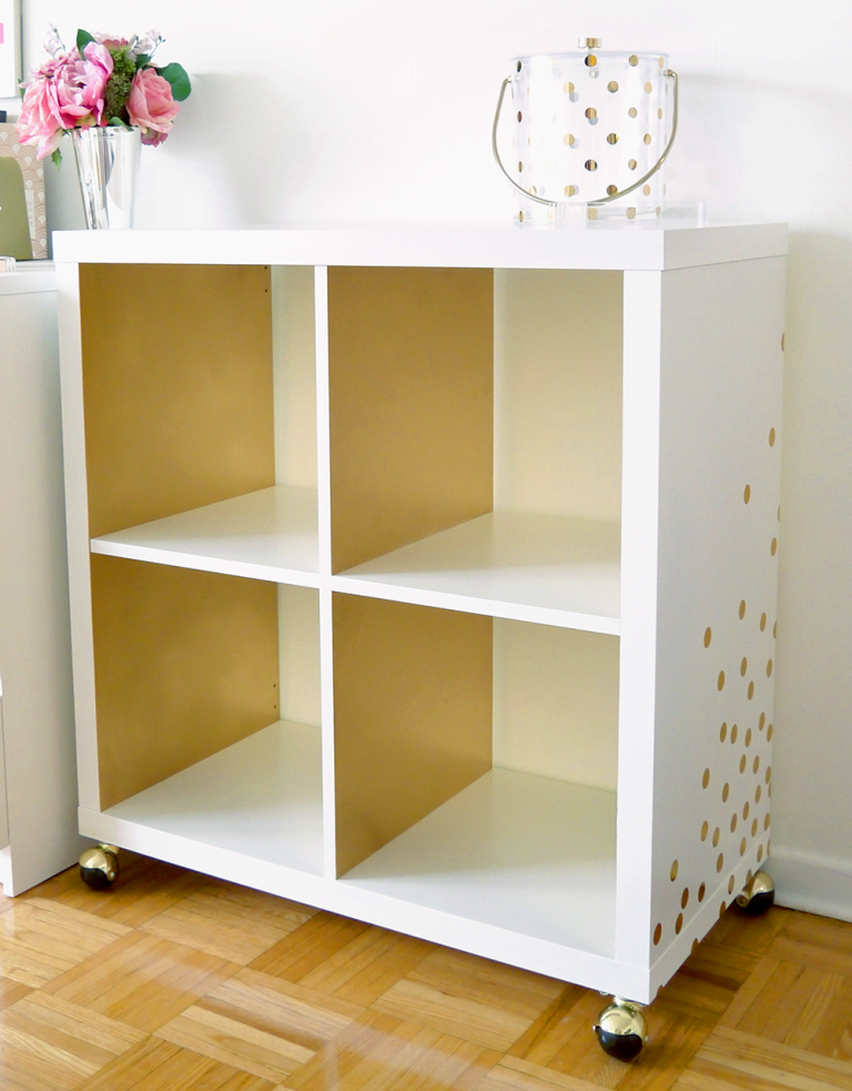an IKEA Kallax shelf on casters, with gold polka dot decals and a matching jar becomes a gorgeous bar cart