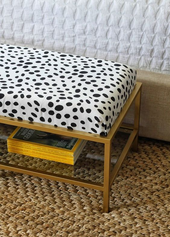 an IKEA Vittsjo table hacked into a chic ottoman with a soft cushion and animal printed fabric on top