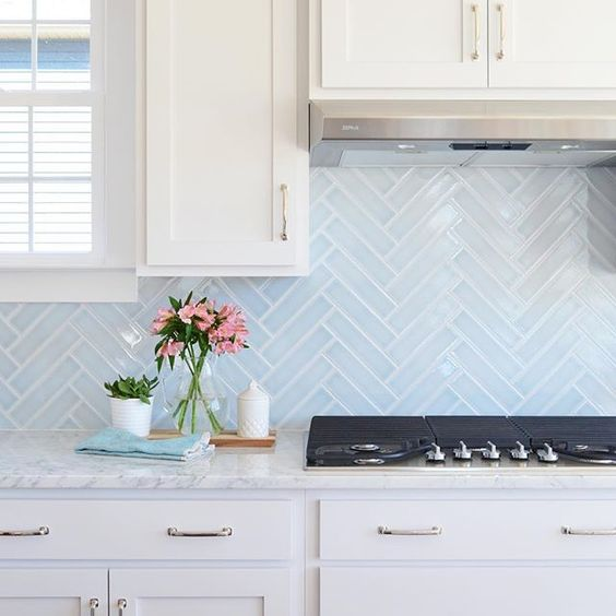 light blue skinny tiles done in a chevron pattern add both pattern and color to the space and make it catchier