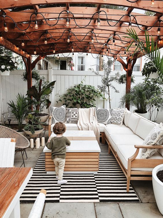 a boho chic patio finished off with a striped rug, potted greenery, printed pillows and lights