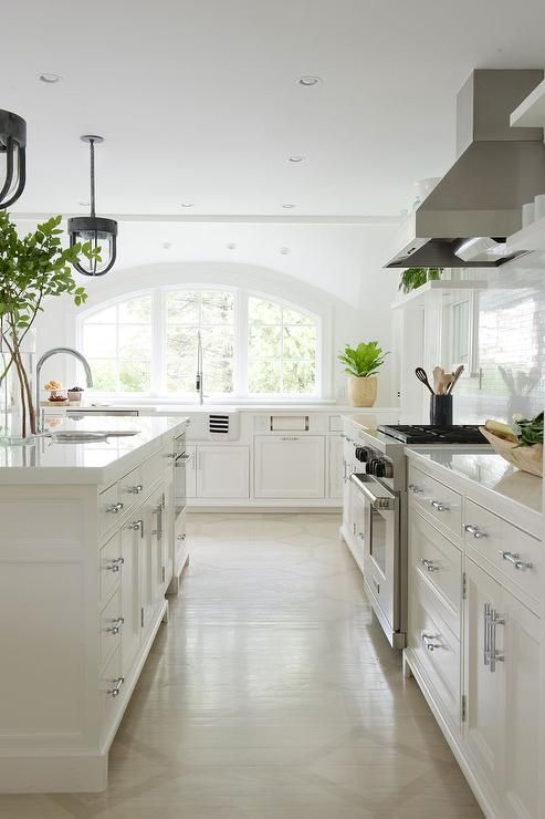 a neutral kitchen with a large arched window that floods the space with light and makes it more chic